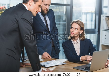 portrait of concentrated lawyers using laptop together during work in office #760344472