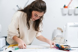 Portrait of concentrated seamstress sewing in the workshop studio