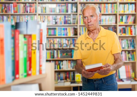 Portrait of concentrated senior man customer visiting bookshop in search of interesting fiction