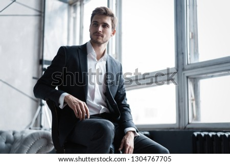 Portrait of confidence. Thoughtful young man in full suit looking away while sitting on the stool. #1304767705