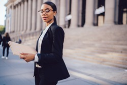 Portrait of confident African American lawyer in stylish eyeglasses and formal apparel holding folder documents in hands while looking at camera. Young female student of high school university