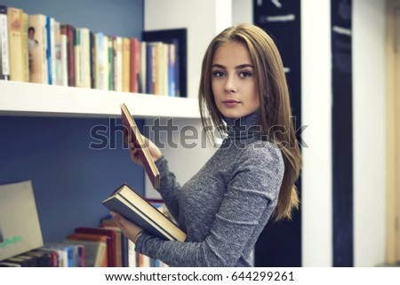 Portrait of confident beautiful teen girl standing in university library and searching interesting literature for improving personal skills and knowledge,charming young woman enjoy leisure time