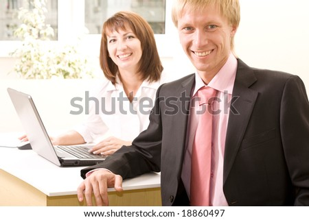 Portrait of confident boss looking at camera with businesswoman near by