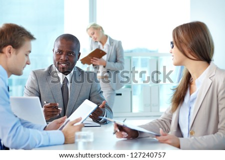 Portrait of confident boss looking at employee during interaction at meeting