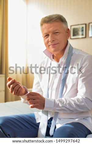 Portrait of confident businessman buttoning sleeve while sitting at home #1499297642