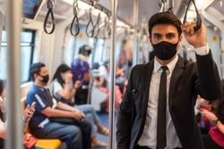 Portrait of confident businessman in black suit wear mask in city finding job during corona crisis using smartphone travelling on empty train