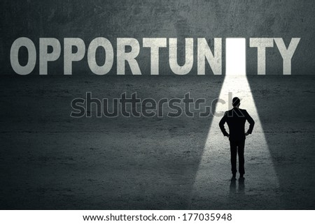 Portrait of confident businessman looking at opportunity door