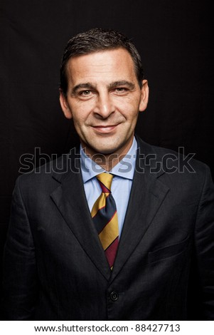 Portrait of confident businessman over black background