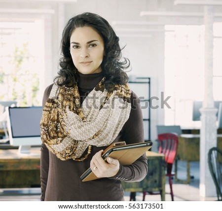 Portrait of confident businesswoman at work standing in loft office smiling