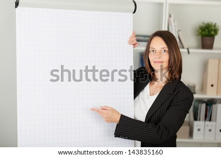 Portrait of confident businesswoman pointing at flipchart in office