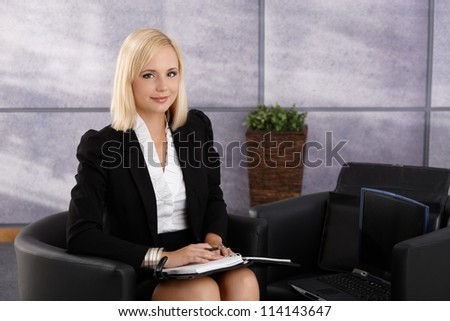 Portrait of confident businesswoman smiling, using personal organizer, sitting in office lobby with laptop computer.
