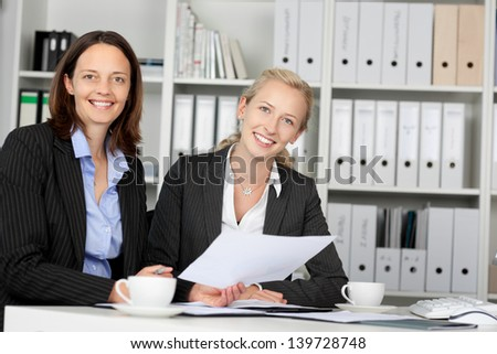 Portrait of confident businesswomen sitting at office desk