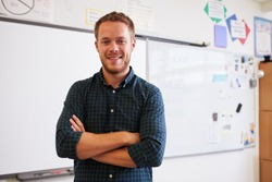 Portrait of confident Caucasian male teacher in classroom