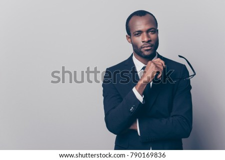 Portrait of confident discerning self-affured chief on a company dressed in black jacket and white shirt holding glasses in hand, isolated on gray background, copy-space