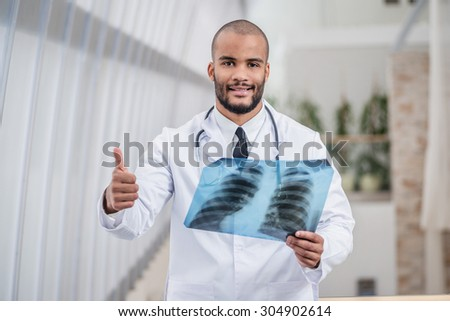 Portrait of confident doctor. Smiling doctor holding X-ray image hands and showing thumbs up and looking at the camera