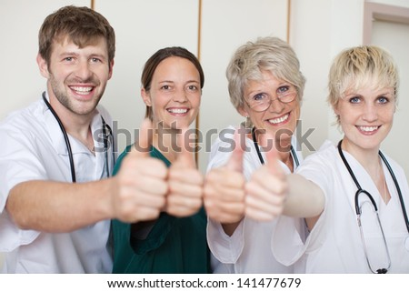 Portrait of confident doctors team showing thumbs up while standing in a row at clinic