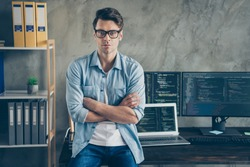 Portrait of confident expert smart guy it manager cross hands work distance ready solve cyber space java script errors bug sit desk wear denim jeans shirt in workplace workstation