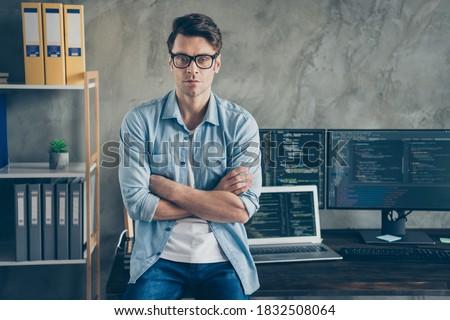Portrait of confident expert smart guy it manager cross hands work distance ready solve cyber space java script errors bug sit desk wear denim jeans shirt in workplace workstation Foto stock ©