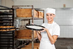 Portrait of confident female baker carrying dough tray at bakery