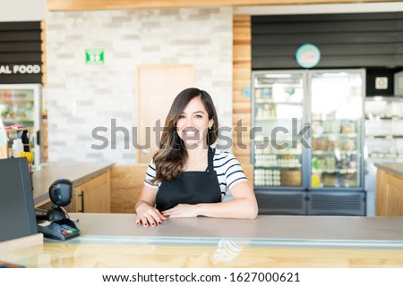 Portrait of confident female cashier at checkout counter in supermarket Сток-фото ©