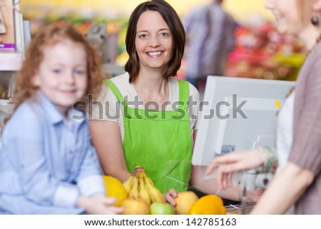 Portrait of confident female cashier smiling with mother and daughter in foreground at supermarket
