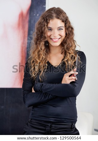 Portrait of confident female hairdresser with arms crossed in salon