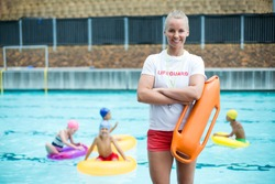 Portrait of confident female lifeguard standing with rescue can at poolside