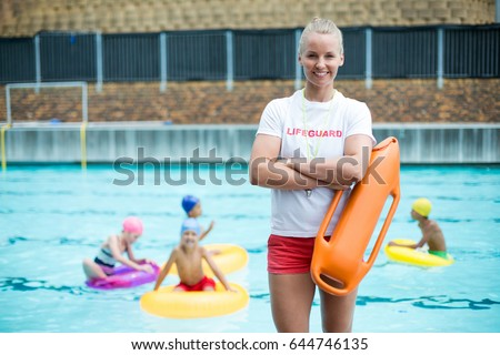 Portrait of confident female lifeguard standing with rescue can at poolside Stockfoto ©