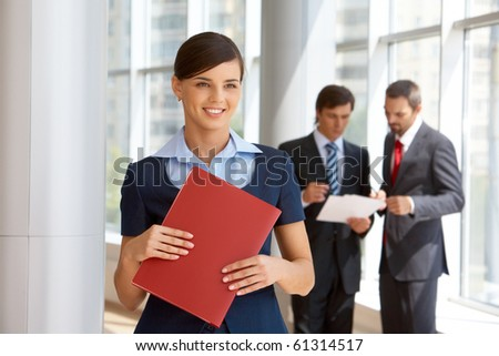 Portrait of confident female looking aside with working colleagues at background