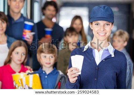 Portrait of confident female worker holding tickets while families waiting in background at cinema