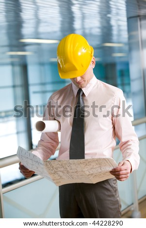 Portrait of confident foreman in helmet learning blueprint