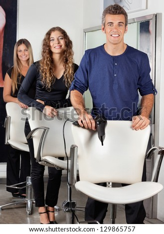 Portrait of confident hairdressers with hairdryer and scissors in salon