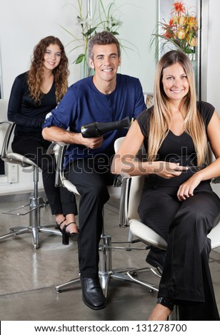 Portrait of confident hairstylists sitting on chairs in salon