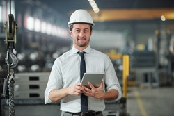 Portrait of confident handsome technical engineer in hardhat using tablet in industrial shop of large plant