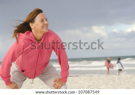 Portrait of confident, healthy and sporty fit attractive looking mature woman in pink sweater, at beach, isolated with storm clouds and ocean as background and copy space.