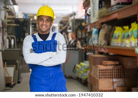 Portrait of confident hispanic storekeeper standing among shelving with goods in building materials store.. Foto stock ©