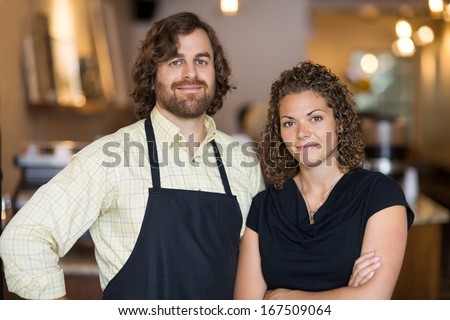 Portrait of confident male and female owners standing together in cafe
