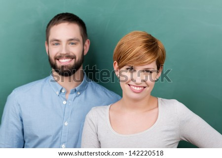 Portrait of confident male and female teachers against chalkboard