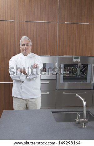 Portrait of confident male chef with arms crossed in commercial kitchen
