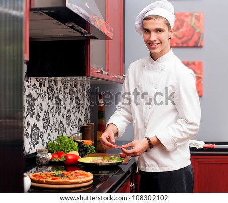 Portrait of confident male cook in modern restaurant kitchen smiling