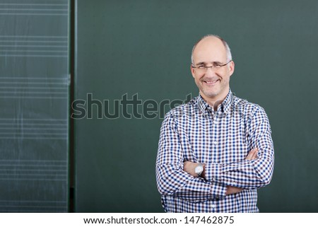 Portrait of confident male professor with arms crossed standing against chalkboard in classroom