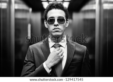Portrait of confident man in suit and sunglasses looking at camera - stock photo