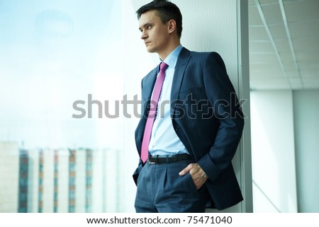 Portrait of confident man looking through window in office