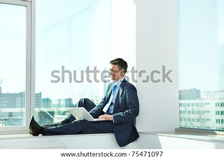 Portrait of confident man sitting with laptop in office
