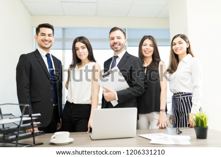 Portrait of confident manager smiling with associates in organization #1206331210