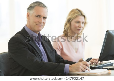 Portrait of confident mature businessman holding pen and mobile phone with female colleague using computer in office