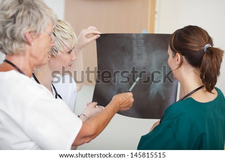 Portrait of confident medical team of female doctors analyzing Xray report in clinic
