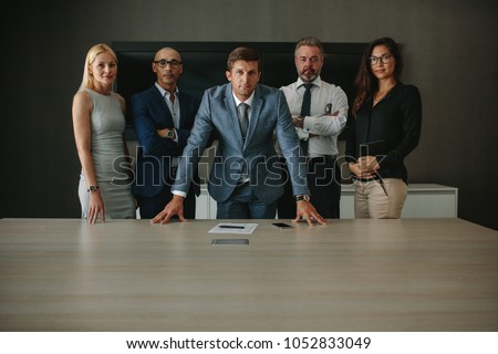 Portrait of confident multi ethnic group of businesspeople looking at camera while standing together at conference table. Corporate professionals in office meeting room. #1052833049