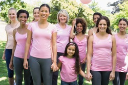 Portrait of confident multiethnic women and girl supporting breast cancer awareness at park