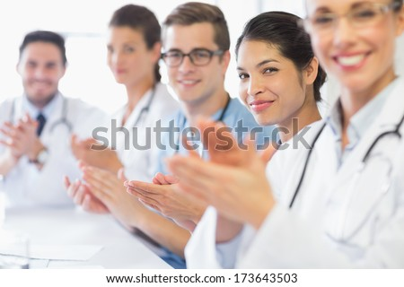 Portrait of confident nurse and doctors applauding in hospital